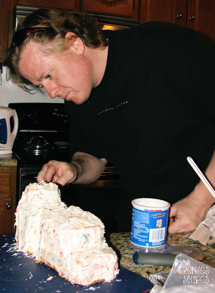 man frosting a lamb shaped cake