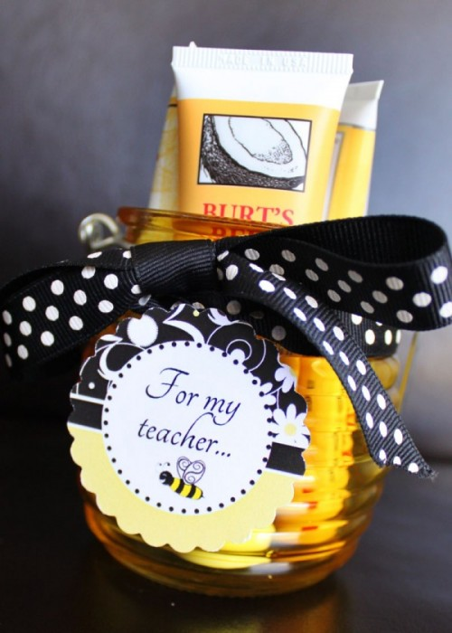 A Beehive shaped jar with a ribbon a tag and lotion tubes inside