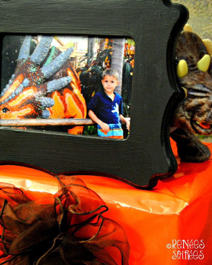 Brown frame with photo of boy and Lego dinosaur on party table