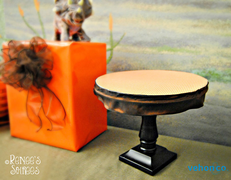 Cake stand with orange top, brown ribbon and brown stand