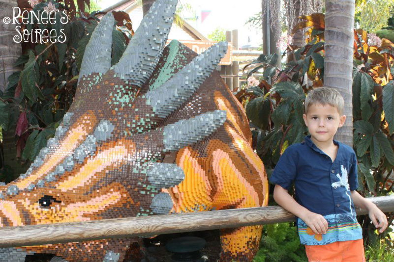 child standing next to a dinosaur made of Legos
