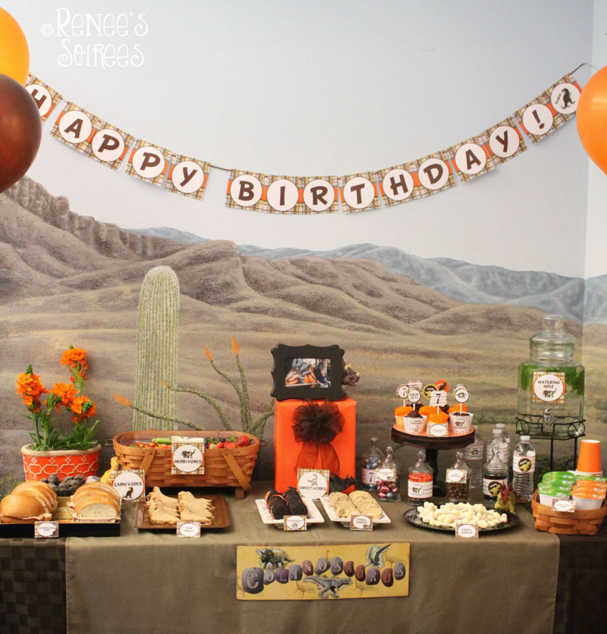 dinosaur-themed party table with banner, food and balloons