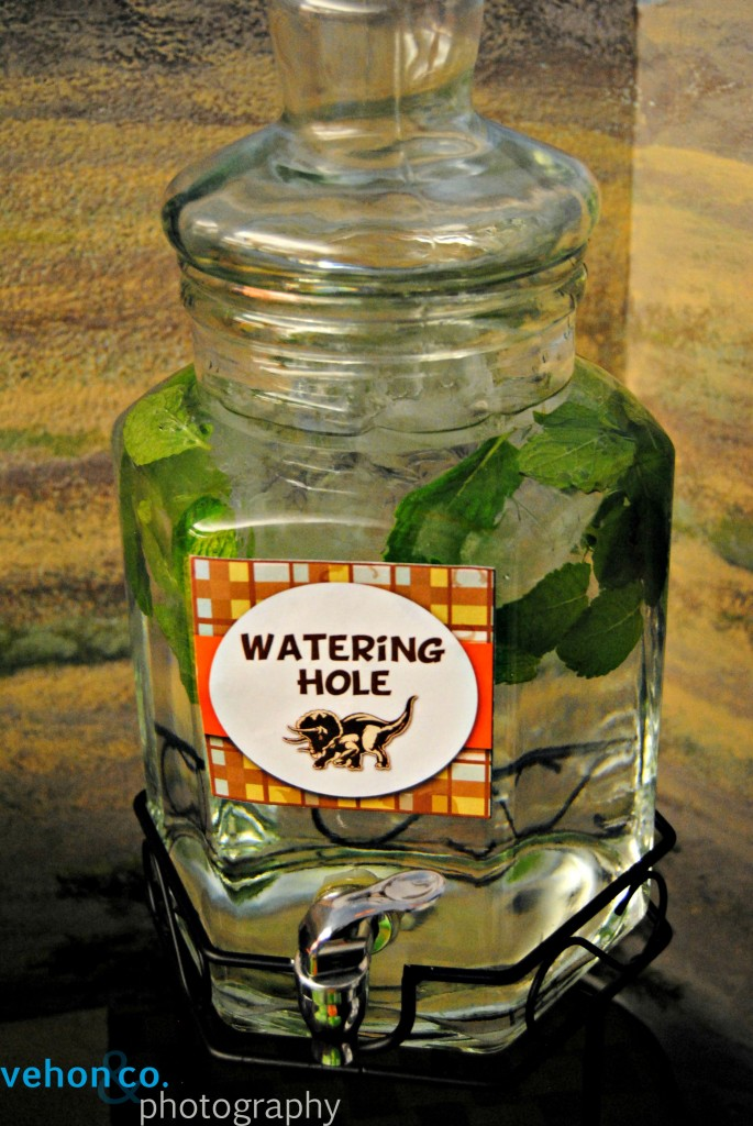 Water jug full of mint leaves and labeled Watering Hole